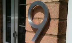 modern house numbers on red brick